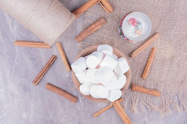 Deliciosos marshmallows em um copo de madeira com paus de canela ao redor