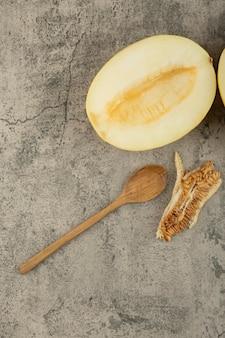 Deliciosos melões amarelos cortados ao meio na superfície de mármore com uma colher de pau de lado.