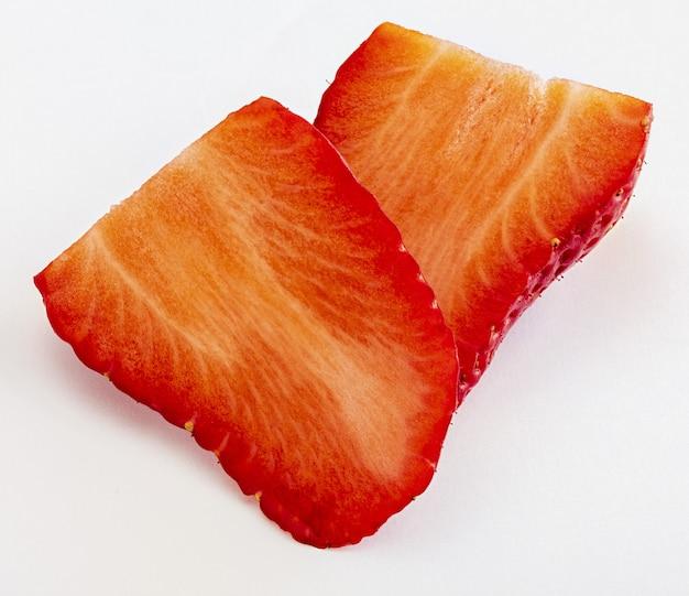 Deliciosos morangos maduros e frescos, cortados ao meio em forma de coração. isolado.