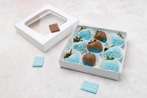 Deliciosos morangos maduros em chocolate marrom e azul, embalado em uma caixa de presente