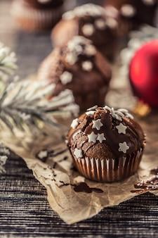 Deliciosos muffins de chocolate de natal polvilhados com topping e estrelas brancas.