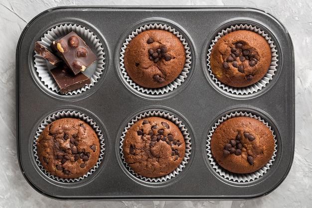 Deliciosos muffins e pedaços de chocolate na mesa