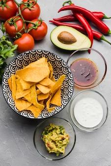 Deliciosos nachos perto de salada entre legumes e molhos