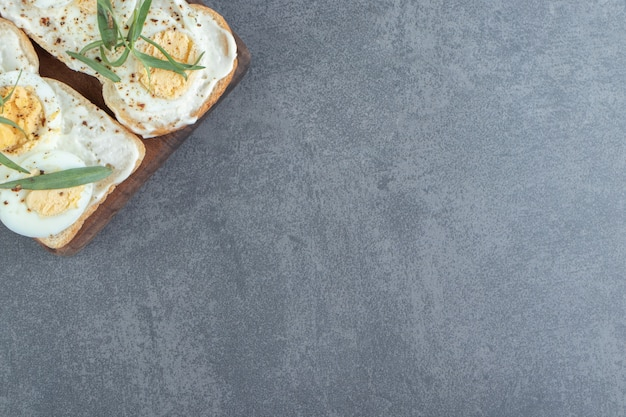 Deliciosos ovos cozidos com torradas de pão na placa de madeira.
