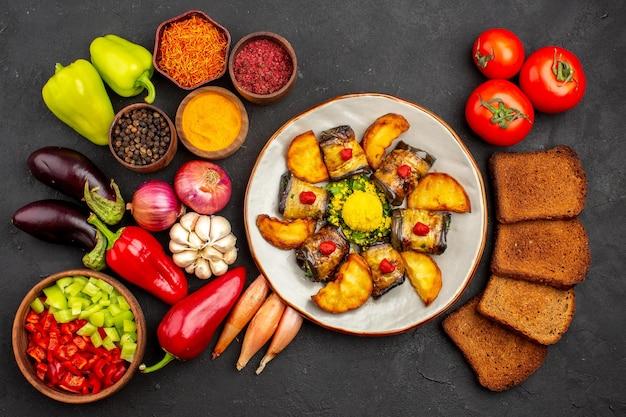 Deliciosos pãezinhos de berinjela com batatas e vegetais frescos em fundo escuro prato jantar refeição madura