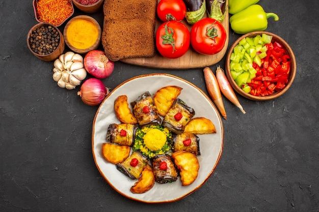 Deliciosos pãezinhos de berinjela com batatas, pão preto e vegetais na superfície escura prato, salada saudável, vista de cima