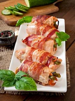 Deliciosos pãezinhos de frango recheados com feijão verde e cenoura embrulhados em tiras de bacon