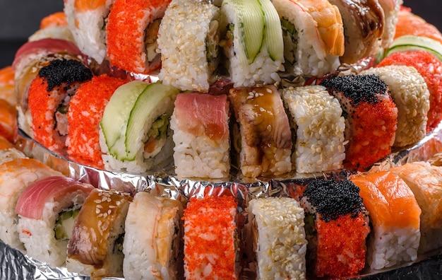 Deliciosos pãezinhos frescos em vários conjuntos. comida japonesa com abacate, camarão, caranguejo e salmão