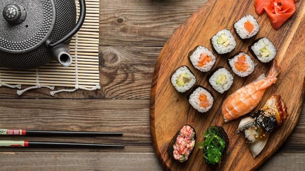 Deliciosos pãezinhos frescos, sushi, gunkan com pauzinhos e bule