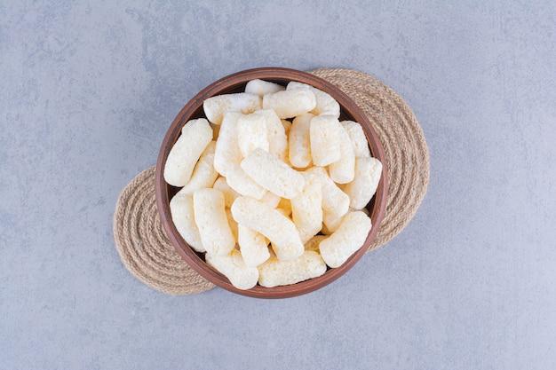 Deliciosos palitos de milho em uma tigela no tripé sobre mármore.