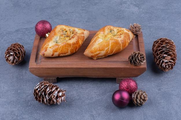 Deliciosos pastéis com bolas de natal em uma tábua de madeira