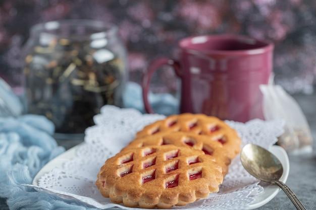 Deliciosos pastéis com xícara de chá e canela em pau.