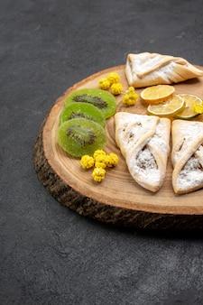 Deliciosos pastéis de frente com anéis de abacaxi seco e kiwis no espaço cinza