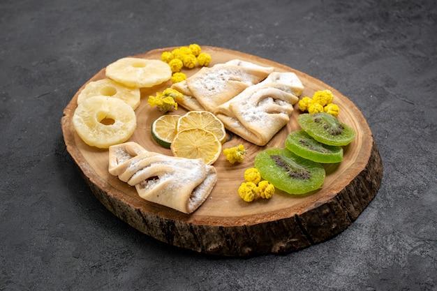 Deliciosos pastéis de frente com fatias de frutas secas em um espaço cinza