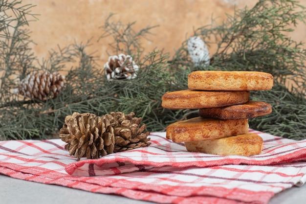Deliciosos pastéis doces com pinhas de natal na toalha de mesa