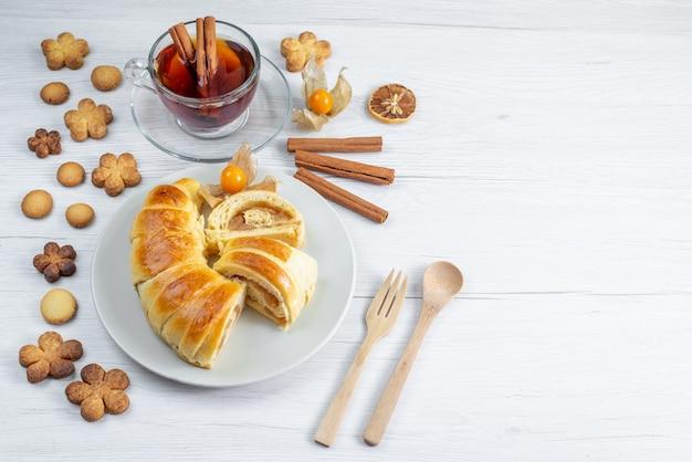 Deliciosos pastéis fatiados dentro do prato com recheio junto com chá e biscoitos no branco