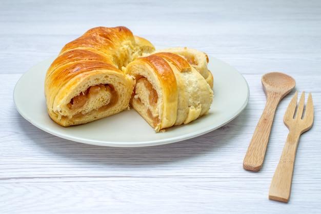 Deliciosos pastéis fatiados dentro do prato com recheio junto com colher de garfo de madeira na mesa branca, biscoito biscoito doce açúcar