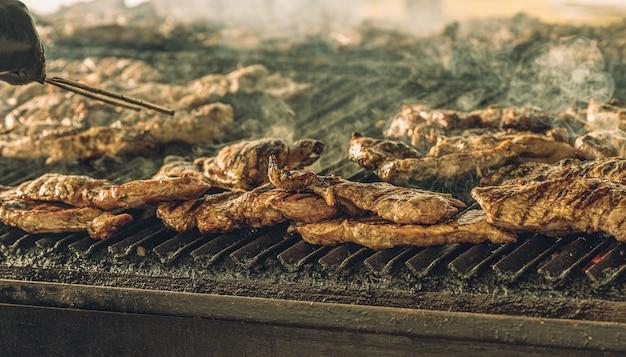 Deliciosos pedaços de carne cozinhando lentamente na churrasqueira de um restaurante.