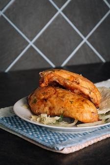 Deliciosos peitos de frango grelhados em um prato no fundo escuro