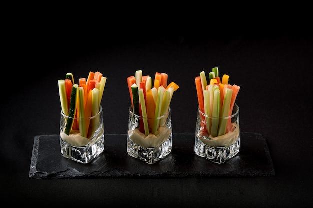 Deliciosos pepinos suculentos, cenouras, aipo, cortados em tiras finas ou clubes, são servidos em um copo de vidro como lanches para mergulhar em um molho picante. fusão conceito de comida, chave baixa, copie o espaço.