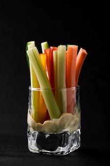 Deliciosos pepinos suculentos, cenouras, aipo, cortados em tiras finas ou clubes, são servidos em um copo de vidro como lanches para mergulhar em um molho picante