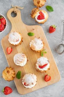 Deliciosos pequenos bolos caseiros profiterole choux pastel com creme, morango e pó de glacê sobre um fundo cinza de concreto. copie o espaço.