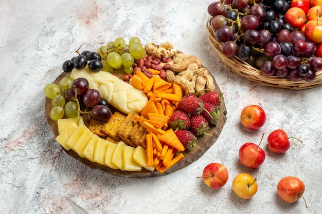 Deliciosos petiscos de vista frontal cips uvas, queijo e nozes no espaço em branco