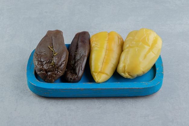 Deliciosos pickles de berinjela e pimentão na placa de madeira, na superfície de mármore