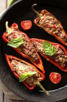 Deliciosos pimentões recheados na frigideira em close-up da mesa