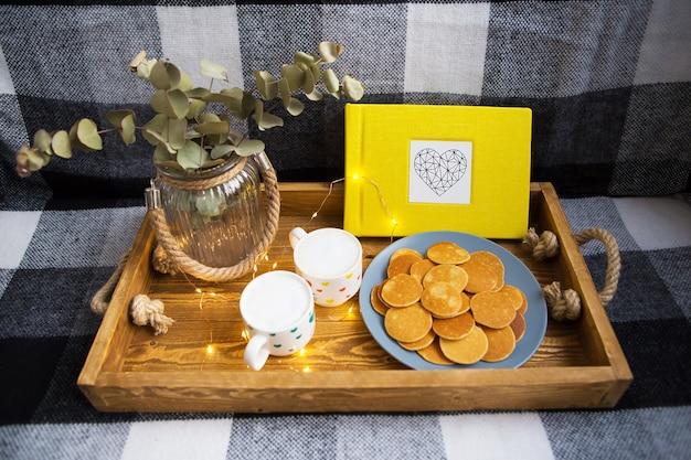 Deliciosos punkcakes e duas xícaras de café em uma bandeja de madeira junto com um álbum de fotos amarelo
