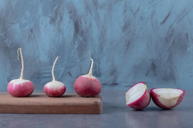 Deliciosos rabanetes com tabuleiro, na superfície de mármore.