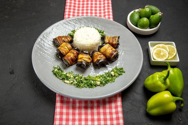 Deliciosos rolos de berinjela em frente ao prato cozido com arroz e diferentes ingredientes na superfície escura cozinhando arroz vegetal comida culinária