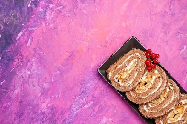 Deliciosos rolos de biscoito com frutas em cima da mesa rosa