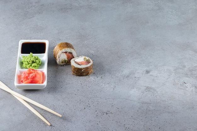 Deliciosos rolos de sushi com atum e molhos na superfície da pedra