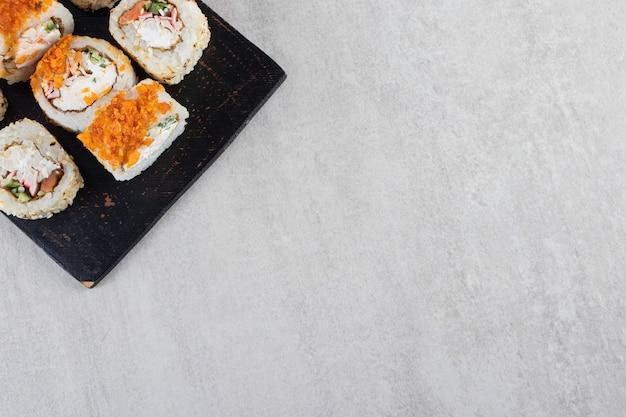Deliciosos rolos de sushi frescos colocados em uma placa de madeira escura.