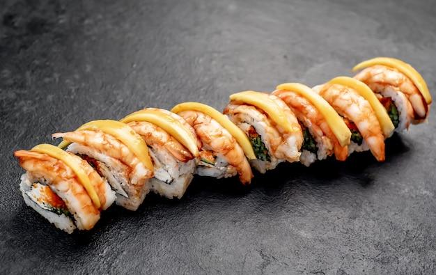 Deliciosos rolos de sushi japonês sobre fundo de pedra prontos para comer