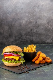 Deliciosos sanduíches caseiros de batata frita nuggets de frango no quadro preto frita pimenta na superfície cinza-escuro borrada