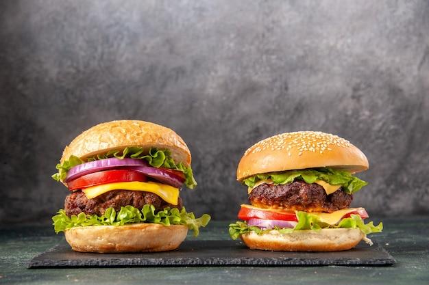 Deliciosos sanduíches caseiros no quadro negro em uma superfície cinza borrada