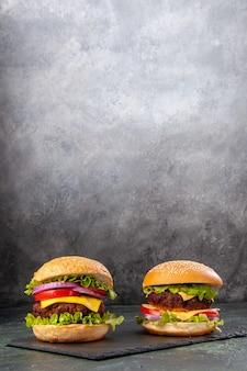 Deliciosos sanduíches caseiros no quadro negro em uma superfície cinza-escura desfocada em visão vertical