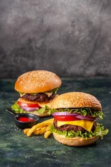 Deliciosos sanduíches de batata frita em uma placa de madeira em uma superfície de cor escura