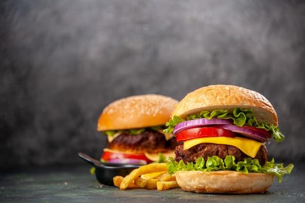 Deliciosos sanduíches de batata frita em uma tábua de madeira no lado esquerdo em uma superfície de cor escura mista