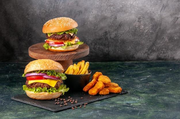 Deliciosos sanduíches de dar água na boca frita nuggets de frango na tábua de corte preta frita pimenta na superfície cinza-escuro borrada