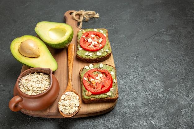 Deliciosos sanduíches de frente com abacate e tomate vermelho sobre fundo cinza.