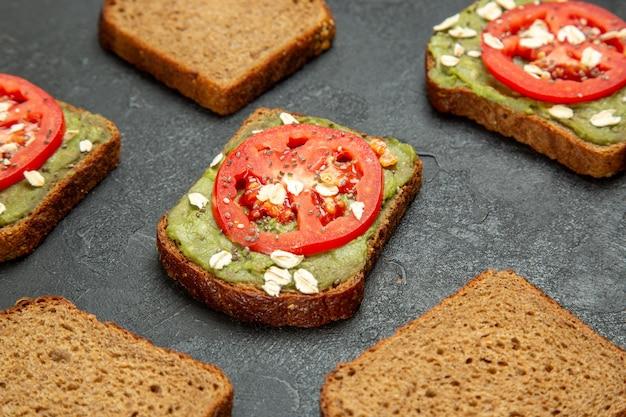 Deliciosos sanduíches de frente com wassabi e tomates vermelhos em um fundo cinza.