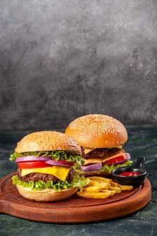 Deliciosos sanduíches de fritas com ketchup em uma placa de madeira em uma superfície de cor escura