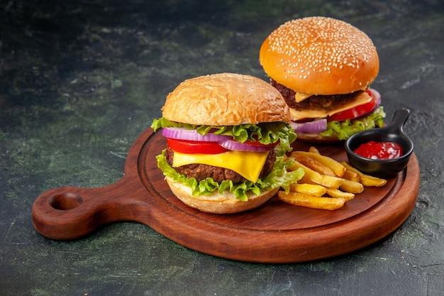 Deliciosos sanduíches de fritas com ketchup em uma tábua de madeira em uma superfície de cor escura