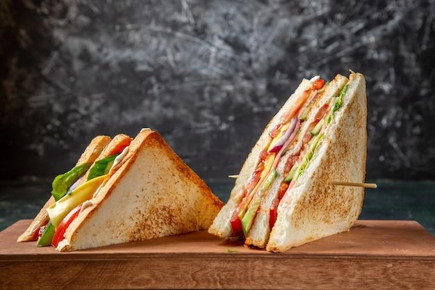 Deliciosos sanduíches de presunto na frente em uma superfície escura de tábua de madeira