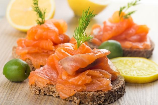 Deliciosos sanduíches de salmão em tábua de madeira