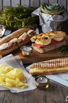 Deliciosos sanduíches e batatas em uma mesa de madeira lindamente decorada