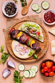Deliciosos vegetais fast-food árabes e carne no espeto plano